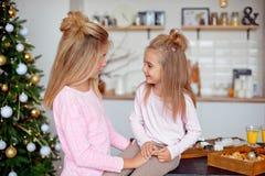Zwei Schwestern in den Pyjamas im Küchenblick auf einander und Lachen Neues Jahr und Weihnachtskonzept stockfotografie