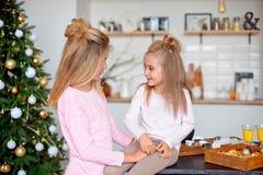 Zwei Schwestern in den Pyjamas im Küchenblick auf einander und Lachen Neues Jahr und Weihnachtskonzept lizenzfreie stockbilder