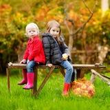 Zwei Schwestern, die auf einer Bank am Herbsttag sitzen Lizenzfreies Stockbild