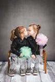 Zwei Schwestern, die auf einer Bank sitzen und geben sich einen Kuss Lizenzfreies Stockfoto