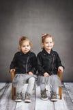 Zwei Schwestern, die auf einer Holzbank sitzen Stockfoto