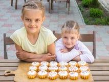 Zwei Schwestern, die bei Tisch sitzen auf, welchen frisch gebackene Ostern-kleine Kuchen sind Stockfoto