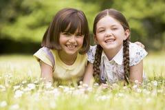 Zwei Schwestern, die draußen lächelnd liegen Lizenzfreie Stockfotos