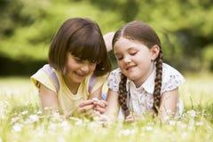 Zwei Schwestern, die draußen mit dem Blumenlächeln liegen Stockfoto