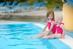 Zwei Schwestern, die durch einen Swimmingpool sitzen Lizenzfreie Stockfotografie