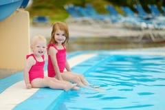 Zwei Schwestern, die durch einen Swimmingpool sitzen Lizenzfreies Stockbild