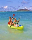 Zwei Schwestern, die einen Kajak in Hawaii schaufeln Stockfotografie