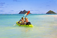 Zwei Schwestern, die einen Kajak in Hawaii schaufeln Stockbilder