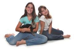 Zwei Schwestern, die ihr junges Kätzchen anhalten Stockfoto