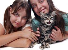 Zwei Schwestern, die ihr junges Kätzchen anhalten Lizenzfreies Stockfoto