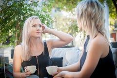 Zwei Schwestern, die Kaffee auf einem Sofa trinken Stockfoto