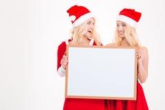 Zwei Schwestern, die leeres Brett halten und auf einander schauen Lizenzfreie Stockbilder