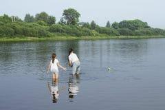 Zwei Schwestern, die mit Papierbooten durch einen Fluss spielen Stockfotos