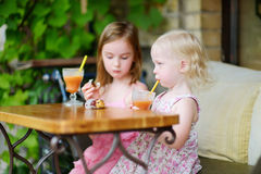 Zwei Schwestern, die Saft trinken und Gebäck essen Lizenzfreie Stockfotografie