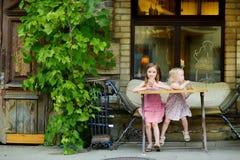 Zwei Schwestern, die Saft trinken und Gebäck essen Lizenzfreie Stockbilder
