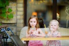 Zwei Schwestern, die Saft trinken und Gebäck essen Stockfoto