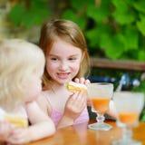 Zwei Schwestern, die Saft trinken und Gebäck essen Stockfotografie