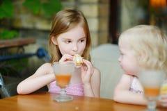 Zwei Schwestern, die Saft trinken und Gebäck essen Lizenzfreies Stockfoto