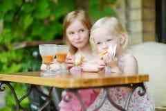 Zwei Schwestern, die Saft trinken und Gebäck essen Stockfotos