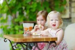 Zwei Schwestern, die Saft trinken und Gebäck essen Stockbild