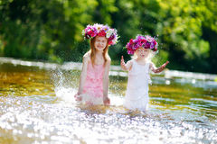 Zwei Schwestern, die Spaß durch einen Fluss haben lizenzfreie stockfotografie