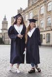 Zwei Schwestern, die zufrieden gestellt glauben, nachdem Diplom erhalten worden ist Stockfotografie