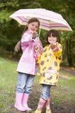 Zwei Schwestern draußen im Regen mit dem Regenschirmlächeln Stockfotografie