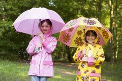 Zwei Schwestern draußen im Regen mit Regenschirmen Lizenzfreie Stockfotografie