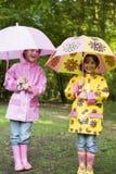 Zwei Schwestern draußen im Regen mit Regenschirmen Stockfoto