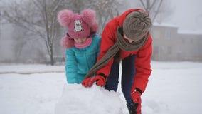 Zwei Schwestern draußen im Winter machen einen Schneemann stock video