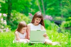 Zwei Schwestern haben einen Spaß mit Laptop Stockbilder
