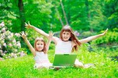 Zwei Schwestern haben einen Spaß mit Laptop Stockbild