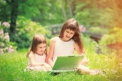 Zwei Schwestern haben einen Spaß mit Laptop Stockfotos