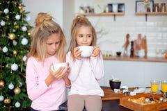Zwei Schwestern in ihren Pyjamas im trinkenden Tee der Küche von der großen weißen Schale auf dem Hintergrund des Weihnachtsbaums lizenzfreie stockfotografie