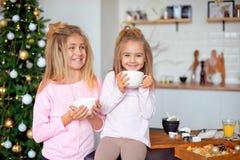 Zwei Schwestern in ihren Pyjamas im trinkenden Tee der Küche von der großen weißen Schale auf dem Hintergrund des Weihnachtsbaums lizenzfreies stockfoto