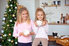 Zwei Schwestern in ihren Pyjamas im trinkenden Tee der Küche von der großen weißen Schale auf dem Hintergrund des Weihnachtsbaums stockfotografie