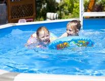 Zwei Schwestern im Bikini nahe Swimmingpool Heißer Sommer Stockfotos