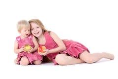 Zwei Schwestern 9-jährig und einjährig mit Apfel Stockbild