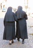 Zwei Schwestern mit schwarzen Kleidern und ein Schleier, die in die Stadt gehen Stockfoto