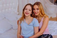 Zwei Schwestern, welche die Pyjamas sitzen auf Bett nachdem dem Aufwachen tragen stockbild