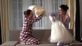 Zwei Schwesterzwillinge, die Spaß mit Lachen und Lächeln haben und mit Kissen am Abend in einem gemütlichen Wohnzimmer kämpfen stock video footage
