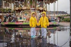 Zwei süße Kinder, Jungenbrüder, aufpassendes Karussell im Regen, Stockfoto