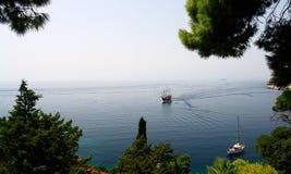 Zwei Segelnboote gesehen durch einige Bäume Lizenzfreies Stockbild