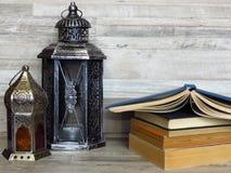 Zwei sehr alte silberne Laternen und ein Stapel von alten Büchern auf gebleichtem Eichenhintergrund lizenzfreie stockfotos