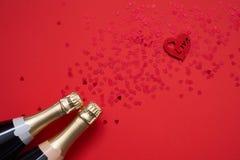 Zwei Sektflaschen mit Konfettiherzen auf rotem Hintergrund Kopieren Sie Raum, Draufsicht stockbilder