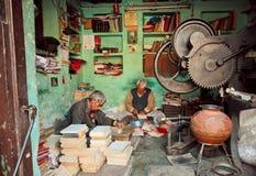 Zwei Senioren, die antike Bücher reparieren Stockfotografie