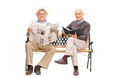 Zwei Senioren, die auf einer Holzbank sitzen Lizenzfreie Stockfotografie