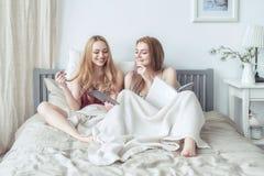 Zwei sexy blonde Mädchen in den Pyjamas, die Spaß im Schlafzimmer haben Junge Frauen, die im Bett unter Verwendung der Tablette l Stockfotos