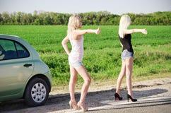 Zwei sexy blonde nahe ihrem unterbrochenen Auto stehende und per Anhalter fahrende Mädchen Stockbild