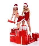Zwei sexy Weihnachtsmädchen, die mit einem Stapel von Geschenken aufwerfen Stockfoto